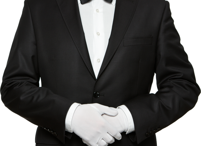 Image of a man wearing a tuxedo with white gloves. Shoulders to hips image